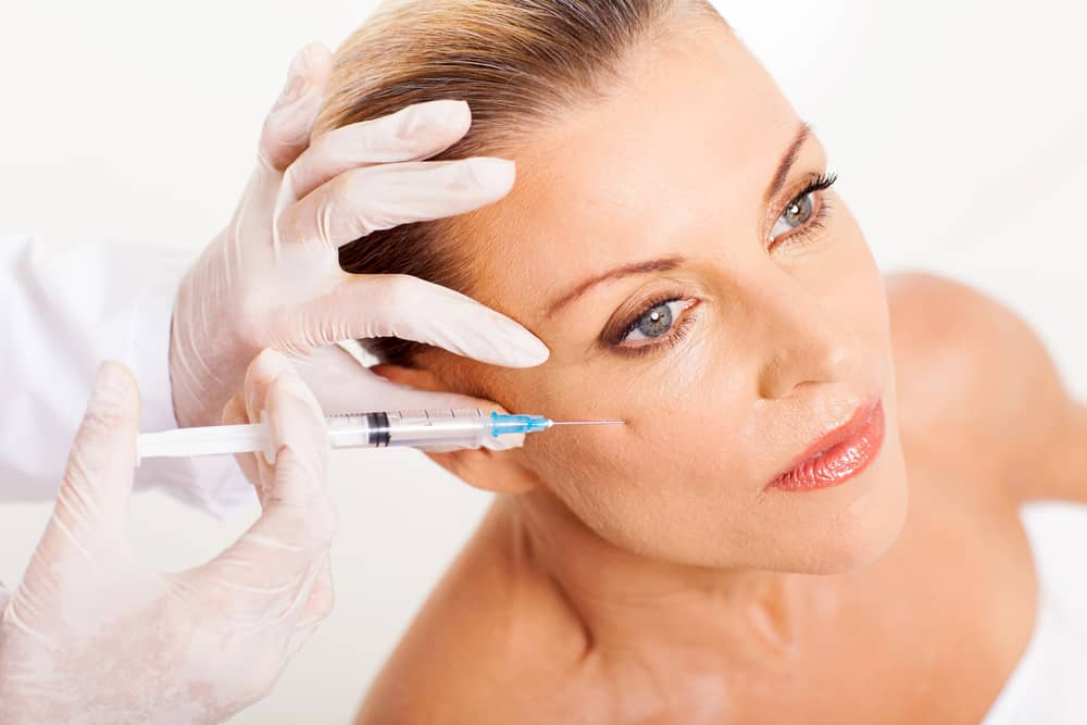 doctor giving mid age woman face lifting injection closeup