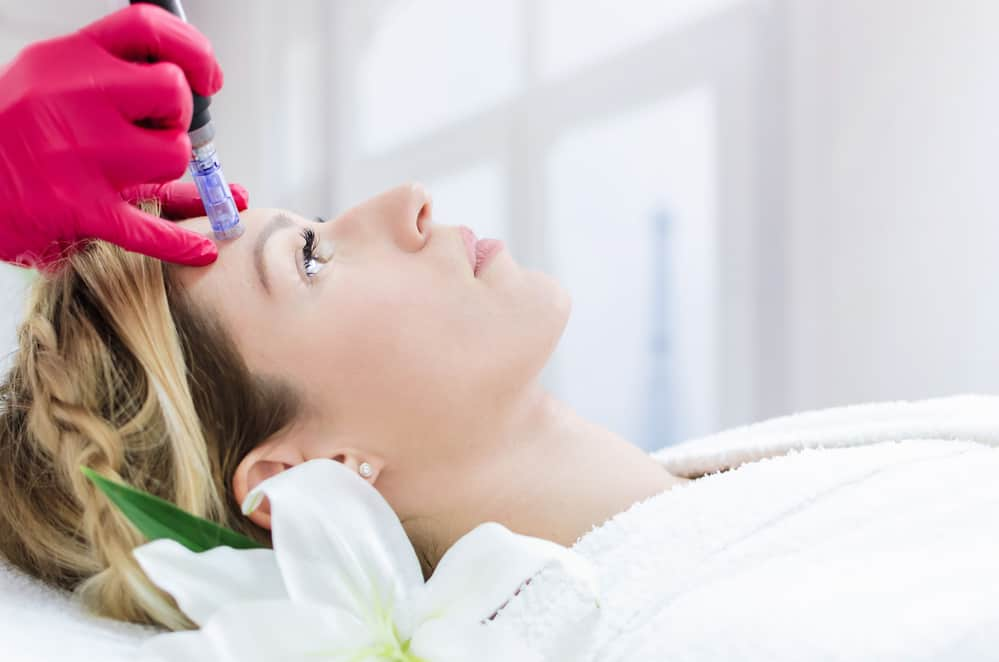Hardware cosmetology, mesotherapy, portrait of young woman getting treatment of forehead zone at spa.